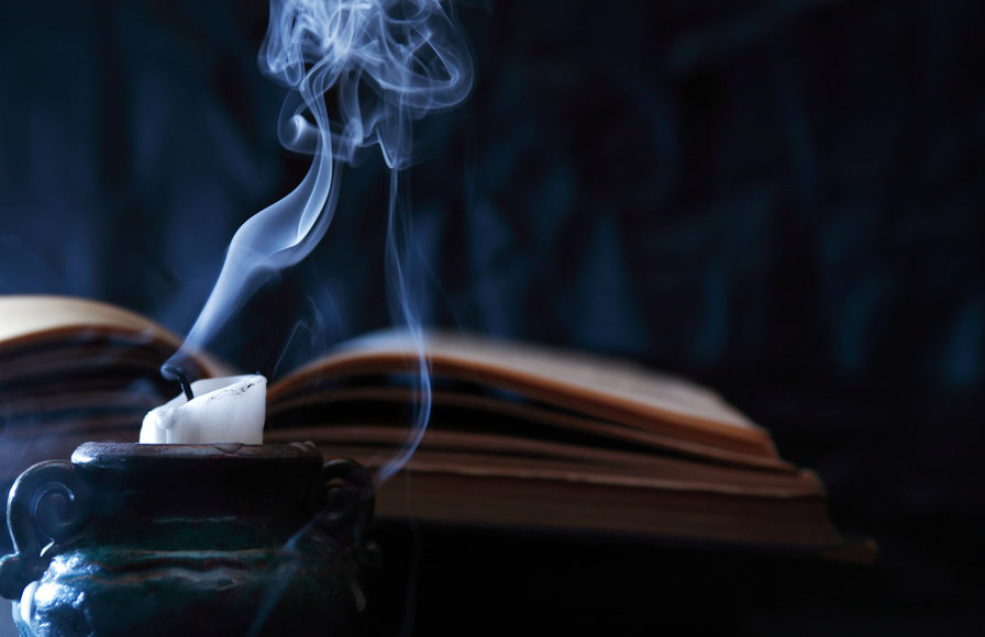 Candle burns out in front of an old book.
