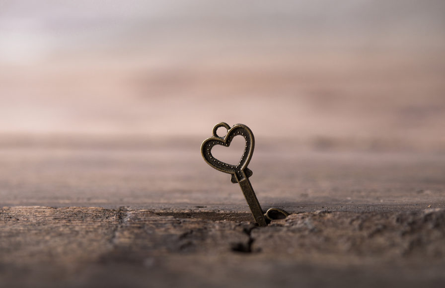 Heart key sticks up out of wooden table.