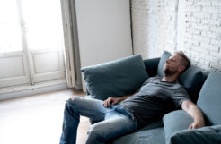 Depression man laying on couch.