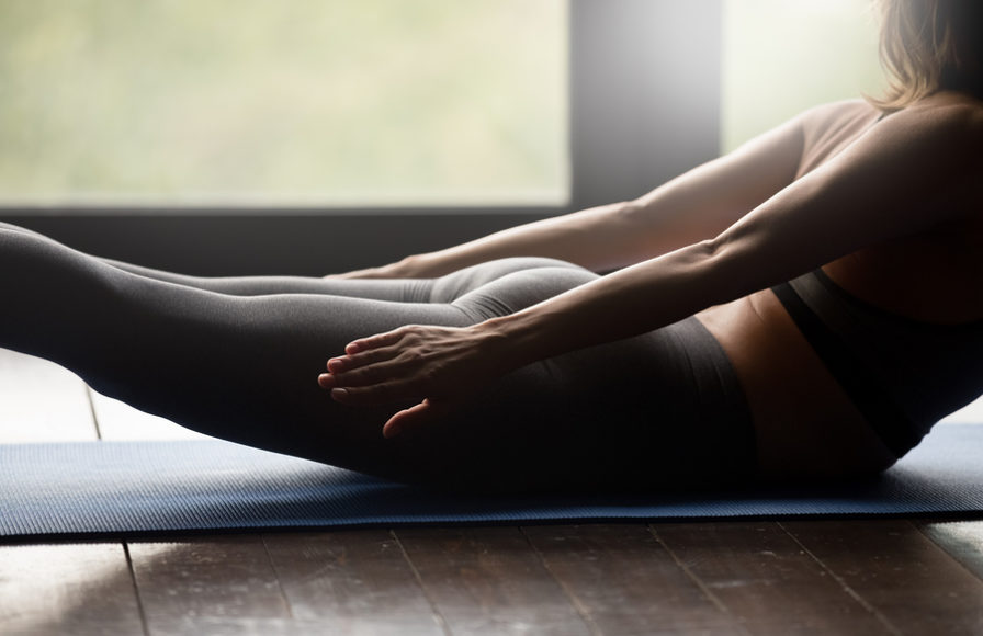 Woman developing proper posture using yoga.